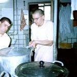Харибол-ананда дас и Навадвипа-Чандра дас поднимают бак на кухне